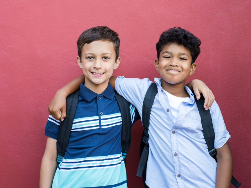 Best children friends standing with hand on shoulder against red background. Happy smiling classmates standing together on red wall after school. Portrait of multiethnic schoolboys enjoying friendship.