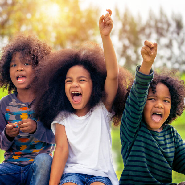 Happy African American boy and girl kids group playing in the playground in school. Children friendship and education concept.
