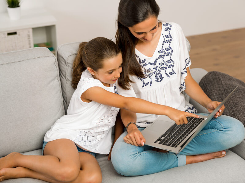 Mom teaching Daughter working with a a laptop at home